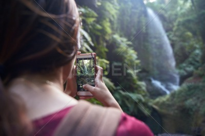 Woman taking a photo of a waterfall