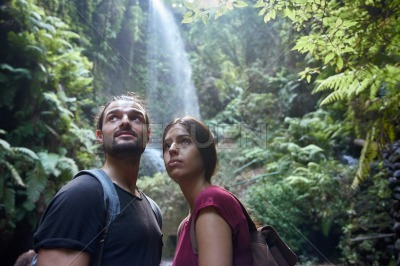 Young couple standing in front of a waterfall