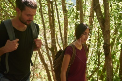Young couple walking past tall thin trees