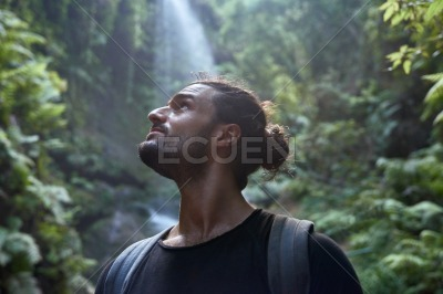 Young man looks up at the waterfall