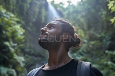 Young man looks up pensively at the trees