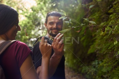 Young man smiles at a woman in a forest