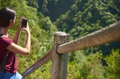 Young woman takes a photo of the valley