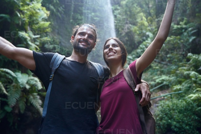 Couple stand smiling as they hold each other stock photo