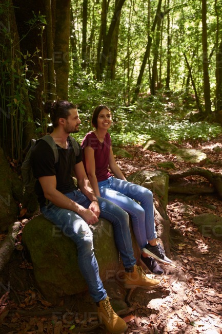 Man and woman sitting resting on a large rock
