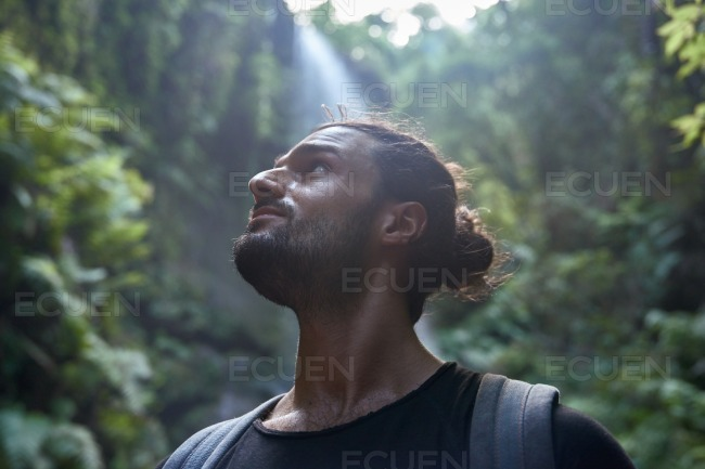 Young man looks up pensively at the trees stock photo