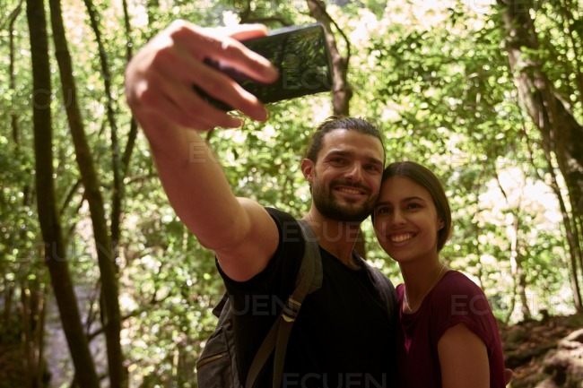 Young man taking a selfie in the forest