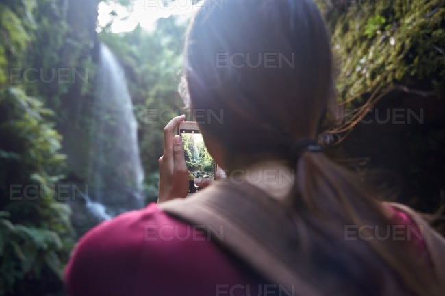 Young woman takes a picture of a waterfall