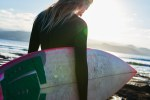 Side view of a girl holding a surf board