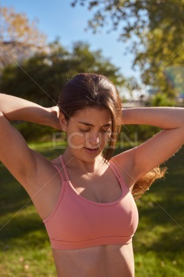 Close up of woman looking down with hands on head