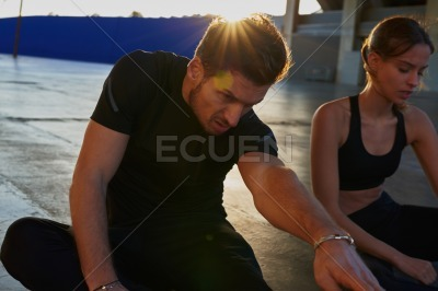 Couple seated and doing stretching exercises