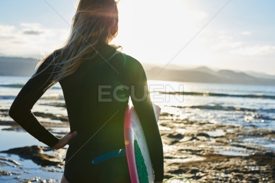 Female surfer in black wet suite at waters edge