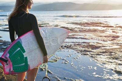 Female surfer standing at the waters edge