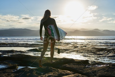 Female surfer standing on the rocks