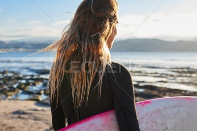 Female surfer staring at the ocean