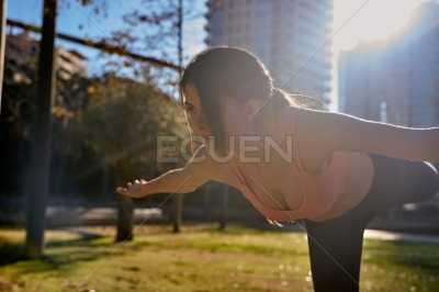Fit woman stands on one leg as she leans foward