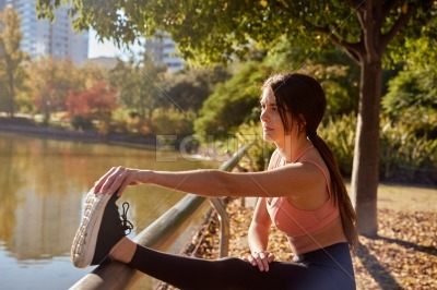 Fit young woman looks ahead as she stretches