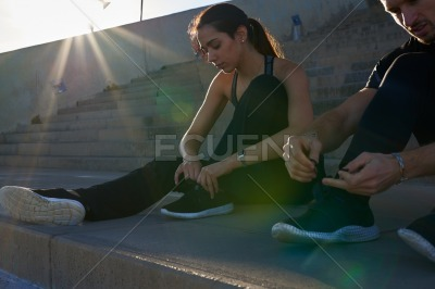 Man and woman leaning forward to tie shoes