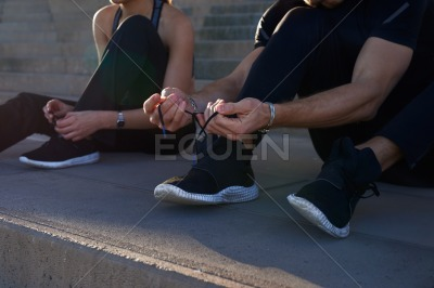 Man seated as he ties his shoe lace