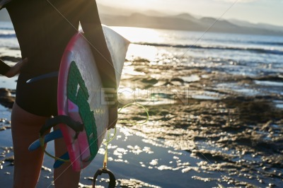 Rear view of a female surfer at the waters edge