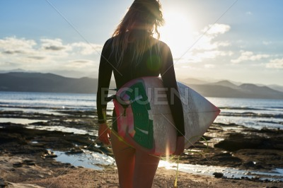 Rear view of a female surfer walking to the sea