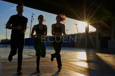 Three joggers running under a concrete bridge