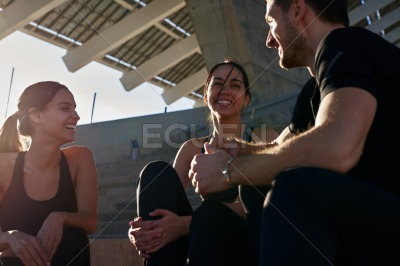 Three people laughing together outdoors in the sun