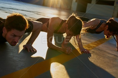 Three young people doing push ups