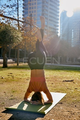 Woman does a head stand pose with twisted legs