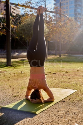 Woman does a head stand yoga pose