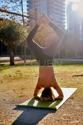 Woman does a yoga lotus head stand in the park