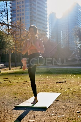 Woman does a yoga tree pose in the park