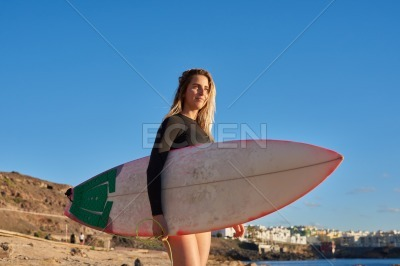 Woman holding a surf board under one arm