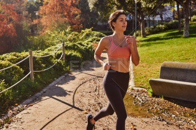 Woman jogger running around a bend in the park