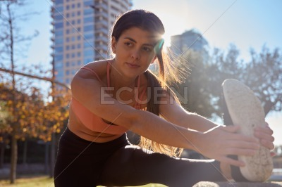 Woman leans and stretches her leg muscles