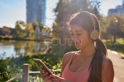 Woman looking at a cell phone wearing headphones
