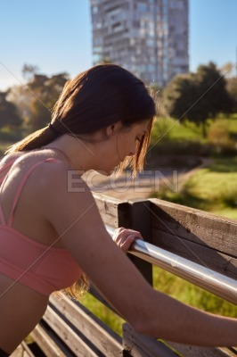 Woman looking down as she holds on to barrier