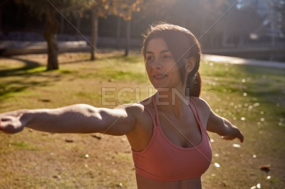 Woman raises her stretched arms to the side