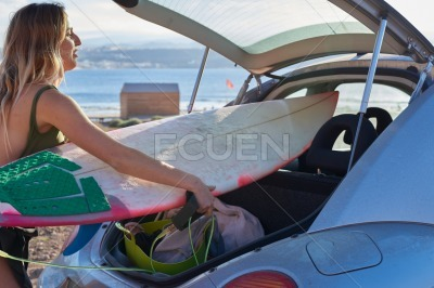 Woman removes a surfboard from the car