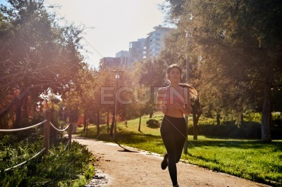 Woman running past trees in the park