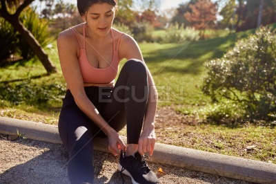 Woman seated on the ground adjusting her shoes