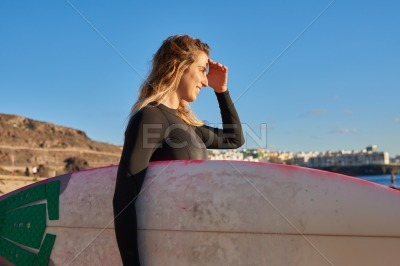 Woman shields her eyes from the sun on the beach