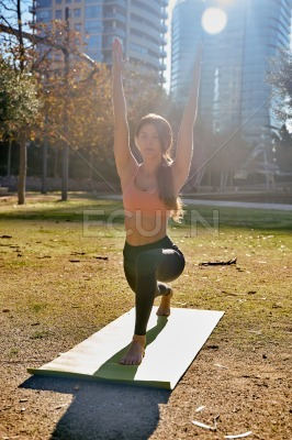 Woman squats down and raises her arms above