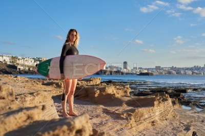 Woman stands on the beach holding a surf board