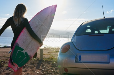Woman walking on the beach with a surfboard