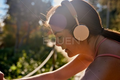 Woman wearing headphones leans forward to stretch