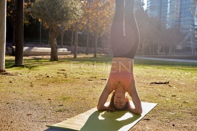 Young woman does a supported full head stand