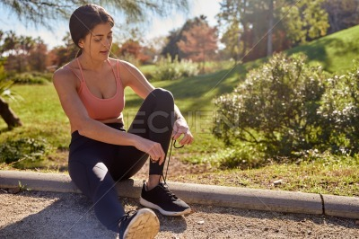 Young woman holds her shoelaces together