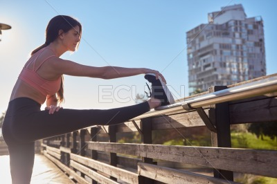 Young woman in pink top stretches her leg upwards