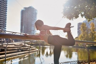 Young woman stretching near a lake